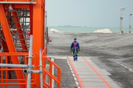 An oil worker walks at an onshore service facility serving installations (one can be seen in the distance) belonging to Kazakhstan's Kashagan offshore oil field in the Caspian Sea in October 2012. With the global benchmark for oil plunging below per barrel last week, Kazakhstan's energy sector is feeling the pinch, leading to a dramatic drop in revenues, and consequent layoffs. (Photo: Joanna Lillis)